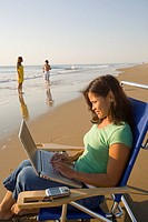 Asian woman typing on laptop at beach