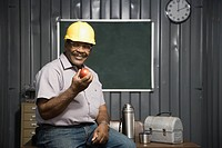 Senior African American male worker holding apple