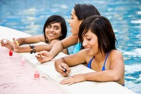 Hispanic teenaged girls painting fingernails in swimming pool