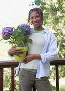 African American woman holding potted plant