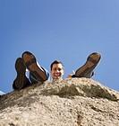 Pacific Islander man sitting on cliff edge