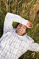 Pacific Islander man laying in field