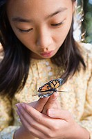 Asian girl holding butterfly