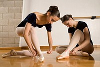 Hispanic female ballet dancers fastening shoes