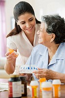 Hispanic woman helping grandmother with medication