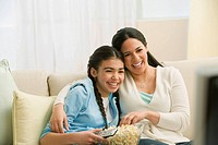 Hispanic mother and daughter watching movie
