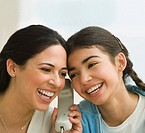 Hispanic mother and daughter listening to telephone