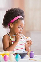 African American girl painting Easter eggs