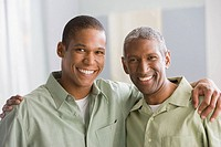 African American father and adult son hugging