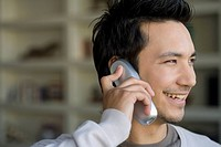Asian man talking on telephone