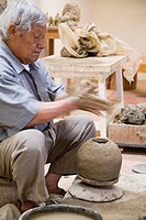 Senior Hispanic man making pottery