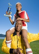 Mixed Race girl on soccer coach&#8217;s shoulders