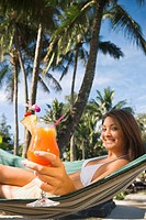 Asian woman with cocktail in hammock
