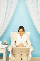Pregnant Mixed Race woman typing on laptop