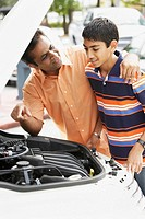 Middle Eastern father and son looking under car hood