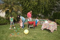 Hispanic family barbequing and playing croquet