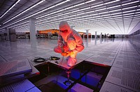 Worker checking floor wiring in semiconductor plant. USA