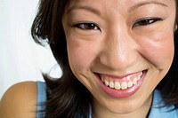 Facial close up of toothy young -mid 20´s- Asian Chinese woman in studio portrait head shot photo shoot