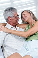 Senior couple being romantic. Woman sitting on mans lap
