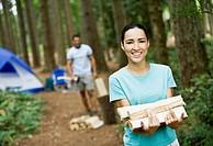 Hispanic woman carrying chopped wood