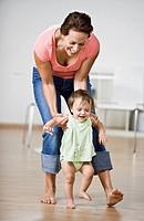 Hispanic mother helping baby walk
