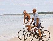 Senior African American couple riding bicycles on beach