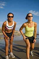 Hispanic female runners racing at beach