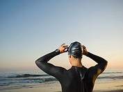Rear view of Hispanic woman wearing wetsuit