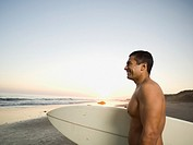 Hispanic man holding surfboard