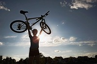 Silhouette of adult lifting mountain bike