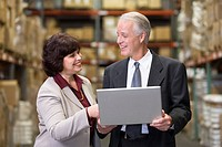 Executives with laptop computer in warehouse