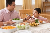 Hispanic father and son at dinner table
