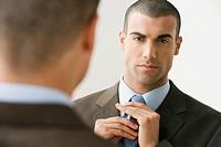 Hispanic businessman adjusting necktie