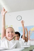 Multi-ethnic children raising hands in class