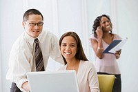 Multi-ethnic businesspeople behind laptop
