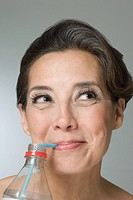 Hispanic woman drinking water