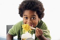 African American boy eating takeout noodles