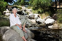 Senior woman sitting beside stream