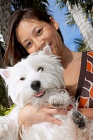Asian woman holding dog