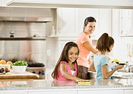 Hispanic mother and daughters cleaning kitchen