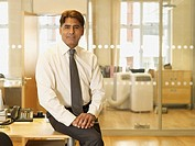 Indian businessman sitting on edge of desk