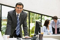 Businessman standing behind his desk