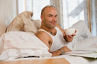 Hispanic man holding coffee mug in bed