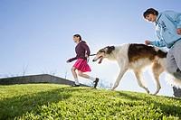 Hispanic brother and sister walking dog