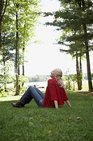 Woman sitting in grass by lake