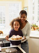 African mother and daughter with tray of cupcakes