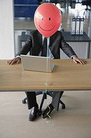 Businessman with smiley face balloon