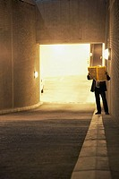 Man reading newspaper in parking garage