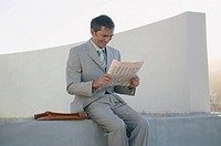 Man reading newspaper outside