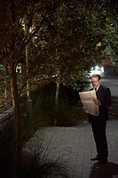 Businessman reading newspaper outside